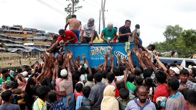 Eine Menschenmenge drängt sich um einen Konvoi mit Lebensmitteln.