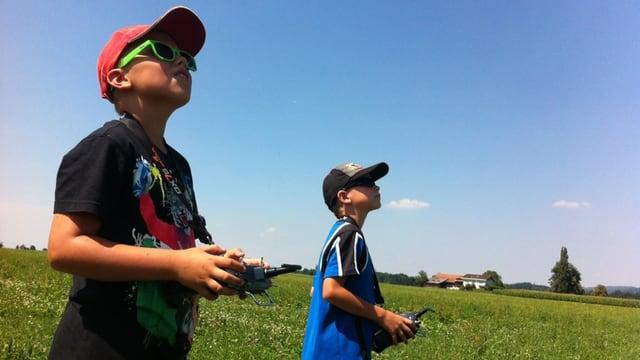 Zwei Knaben halten eine Drohnen-Fernsteuerung in der Hand und schauen in die Luft.