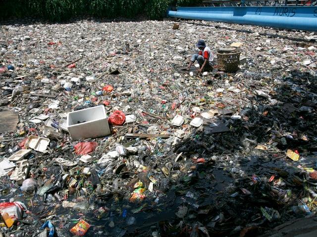 Person sitz inmitten von Müll in Djakarta, Indonesien