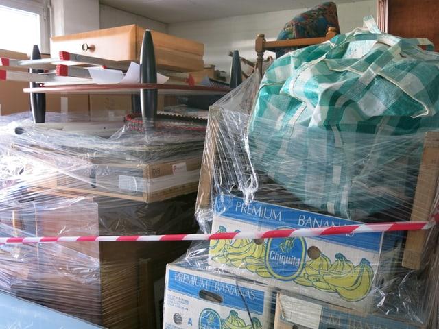 Kisten, Möbel und Plastiksäcke im Depot.
