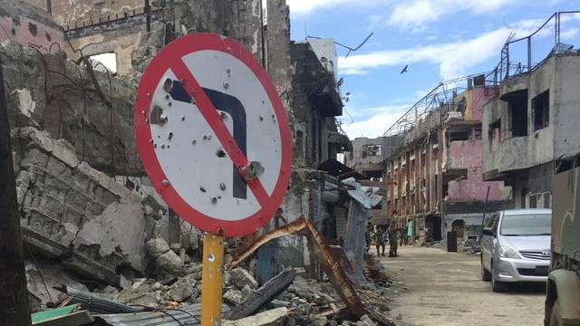 Ein zerschossenes Strassenschild, zerstörte Häuser entlang einer Strasse.