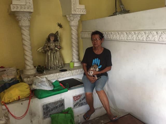 Tita sitzt mit ihrem kleinen Hündchen im Mausoleum.