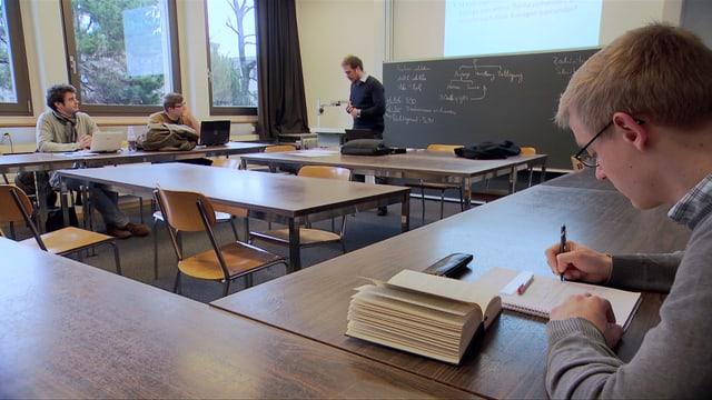 Drei Studenten in einem Klassenzimmer.