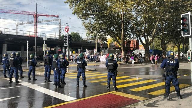 Polizisten stehen auf der Strasse gegenüber von Protestierenden.