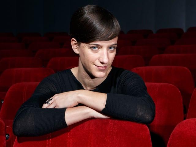 Eine junge Frau allein in einem Kinosaal.