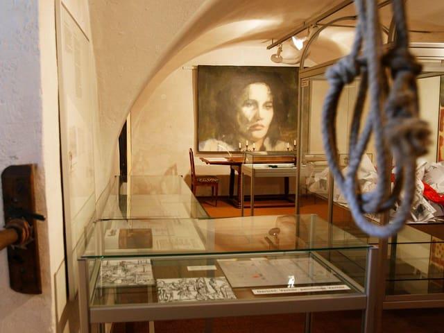 Blick in einen Ausstellungsraum mit grossem Porträt und Vitrinen.