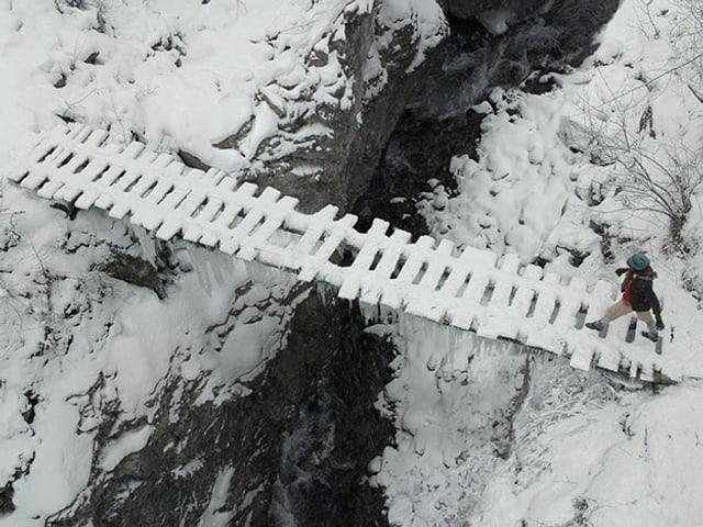 Schellenursli geht über eine verschneite Holzbrücke über der Schlucht.