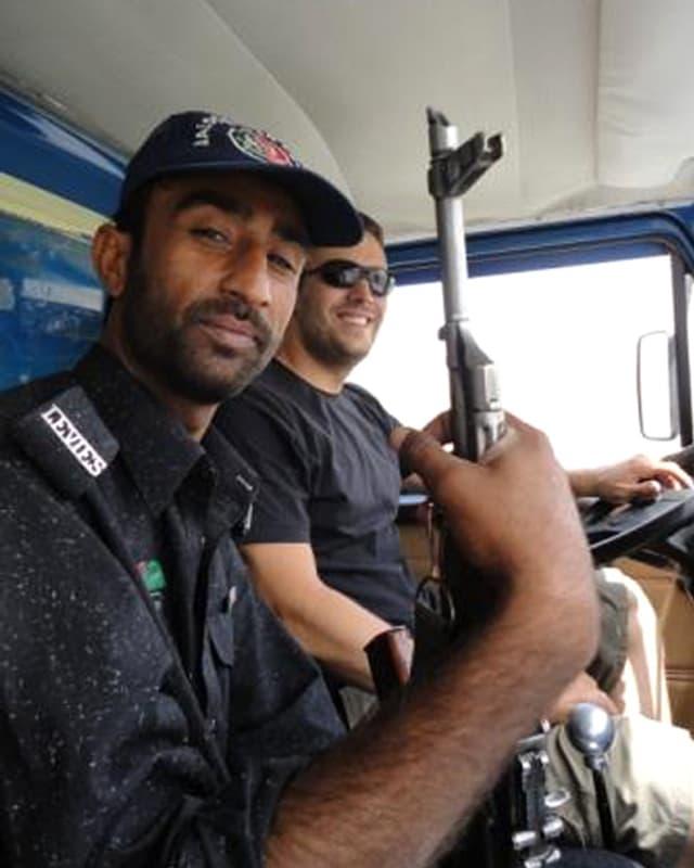 Ein Polizist mit einem Gewehr in der Hand in der Führerkabine neben David Och.