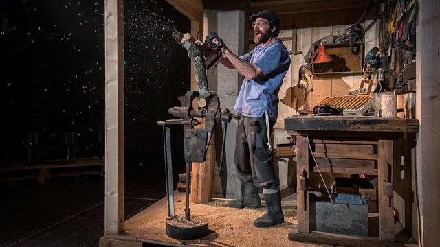 Ein Schauspieler schnitzt eine Puppe aus Holz.