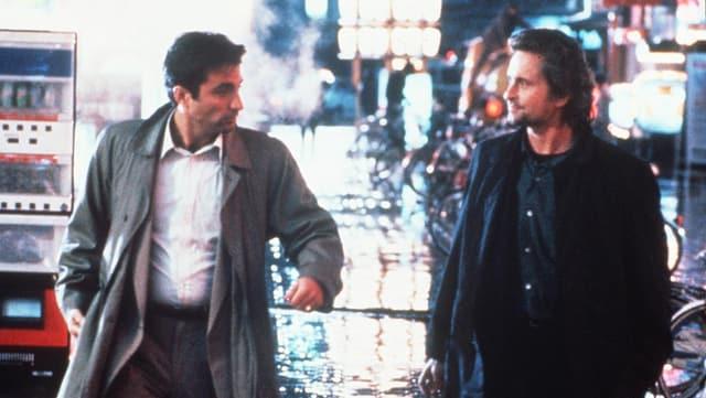 Zwei Männer laufen nachts auf einer Strasse.