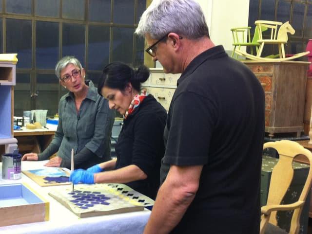 Daniel, Patrizia und Anet: Anet stupft mit einem Pinsel Farbe auf das Holz.