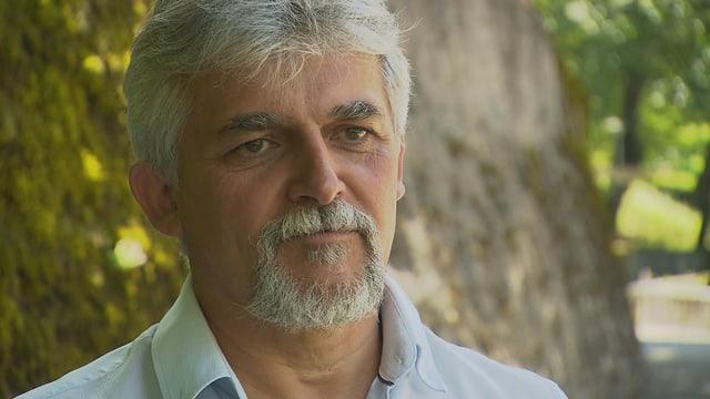 Portrait da Fernando Giovanoli - in um cun chavels curts alvs ed ina barba alva.