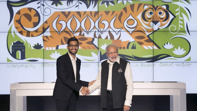 """Zwei Männer vor der Zeichnung eines Tigers mit der Aufschrift """"Google""""."""