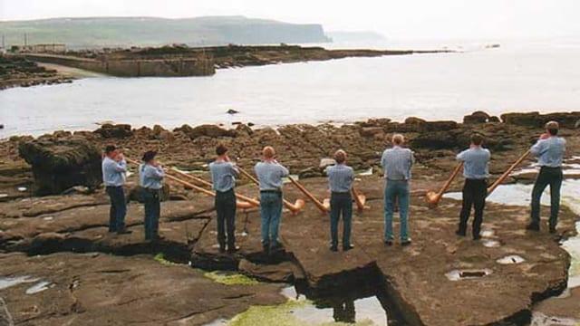 Gruppe von 8 Alphornbläsern auf Felsen an der Meeresküste.