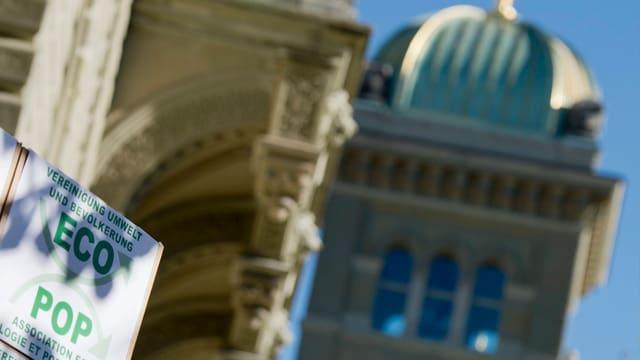 Bundeshauskuppel im Hintergrund, am Rand eine Kartonschachtel, die mit ECOPOP angeschrieben ist.