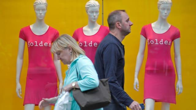 Ein Mann und eine Frau gehen an drei «Soldes»-Kleidchen tragenden Schaufensterpuppen vorbei.