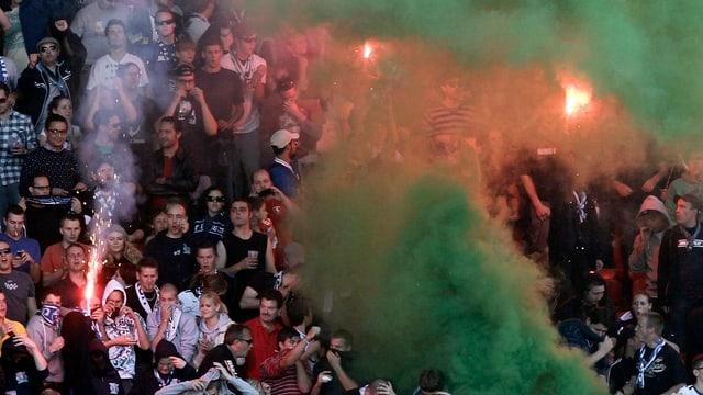 Grüner Rauch über einer Menge Fussballfans.