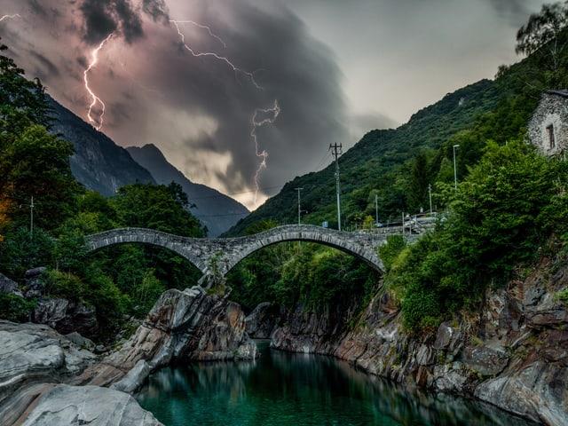 Steiniger Fluss mit alter Steinbrücke. Im Hintergrund dunkle Wolken mit Blitzen. Es scheint Dämmerung zu sein.