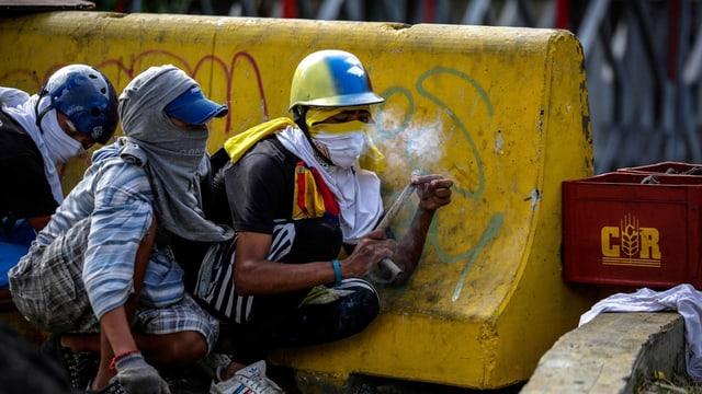 Purtret da trais demonstrants mascrads che sa zuppan davos in bloc da betun.