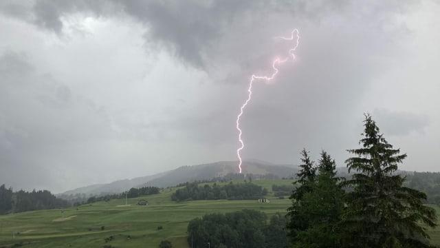Oberhalb von Savognin schlägt ein Blitz in der Wiese ein.