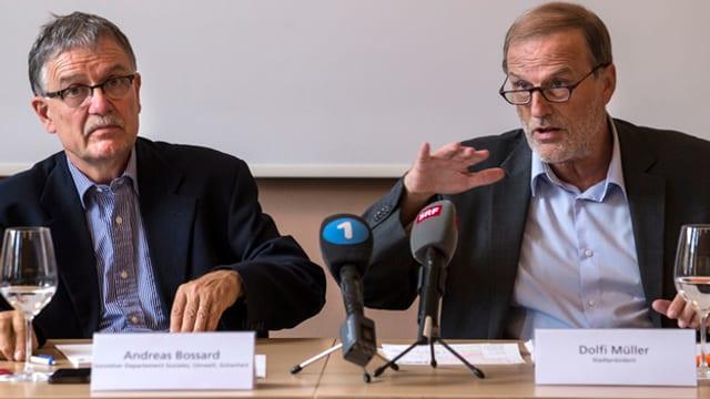 Zwei Männer sitzen an einem Tisch mit Mikrophonen drauf.