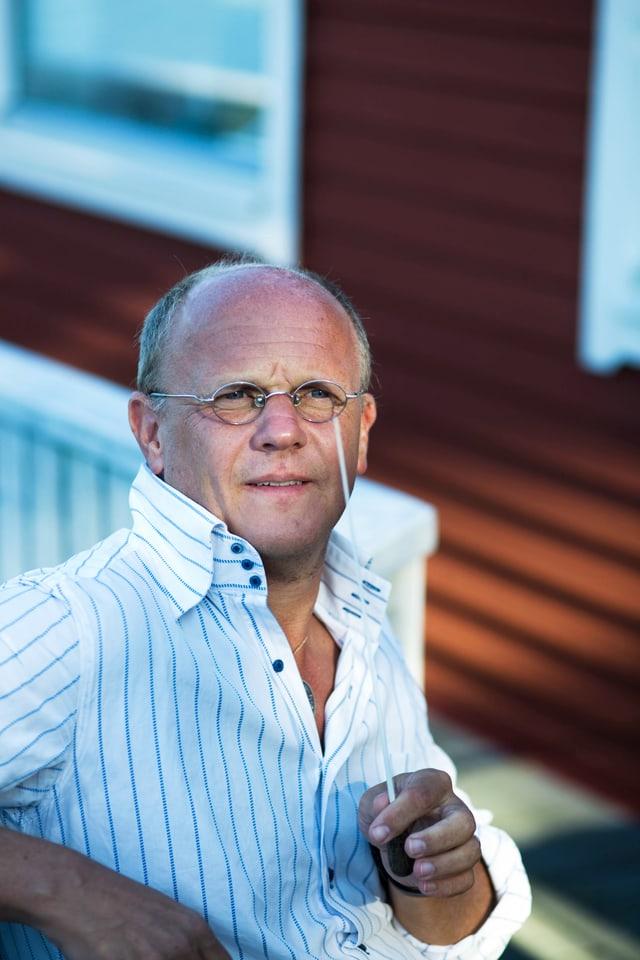 Ein Mann sitzt mit einem Takstock in der Hand vor einem Haus.