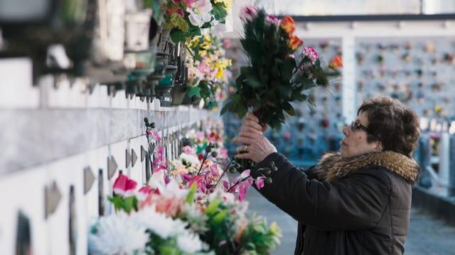 Eine Frau bringt Blumen an ein Grab.