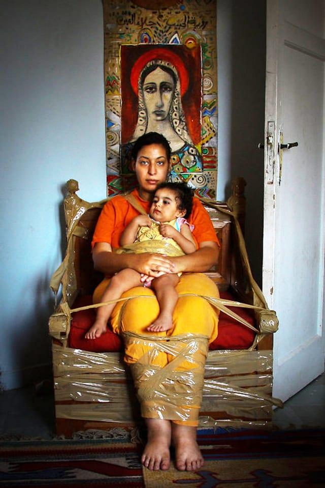 Heba Khalifa mit Baby an einen Stuhl gefesselt