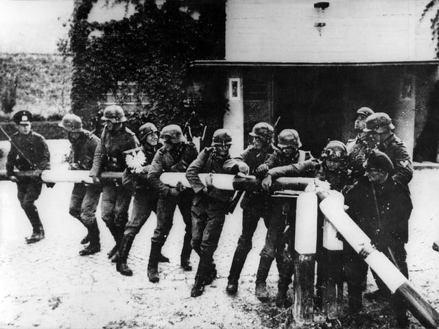 Wehrmachtssoldaten reissen am 1. September 1939 einen Schlagbaum an der deutsch-polnischen Grenze ein.