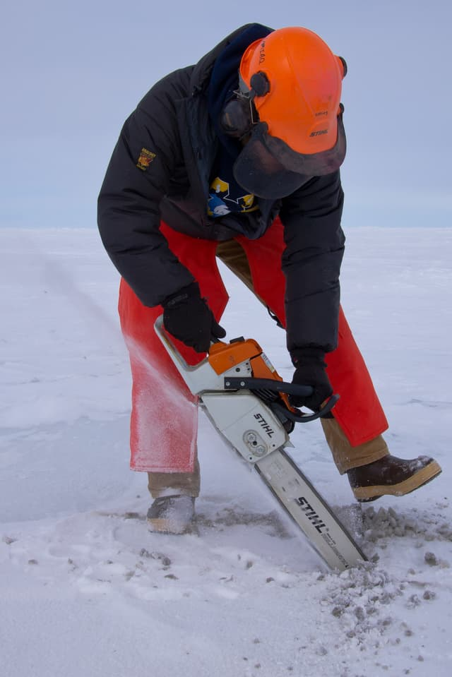 Ein Mann sägt mit einer Motorsäge ins Eis.