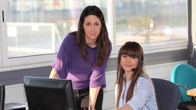 Zwei Frauen in einen Büro. Eine Frau steht, die andere sitzt und trägt einen Kopfhörer zum Telefonieren