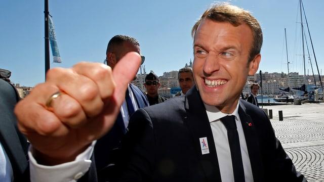 Emmanuel Macron lachend in Nahaufnahme mit hoch gerecktem Daumen.