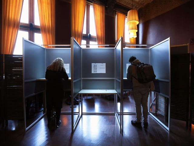 Eine Frau und ein Mann füllen ihren Wahlzettel aus.