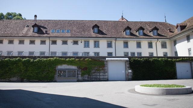 Altes Gebäude mit Ziegeldach, grüne Hecke und Zaun