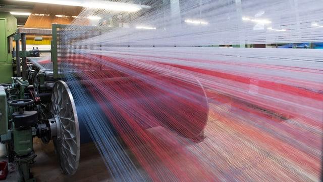 Blick auf eine Textilmaschine, in der zahlreiche Fäden verwoben werden.