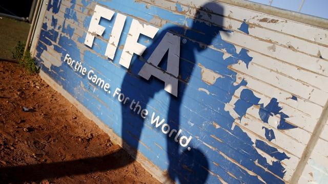 Schatten eines Fussballers auf einer Bretterwand mit Fifa-Logo
