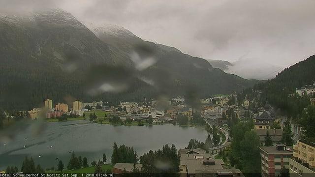 Blitz auf St. Moritz mit See und an die Berghänge. In den oberen Teilen der Hänge liegt etwas Schnee.