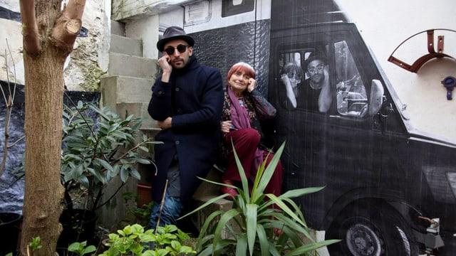 Street-Art-Künstler JR und Agnès Varda vor einer bemalten Wand.