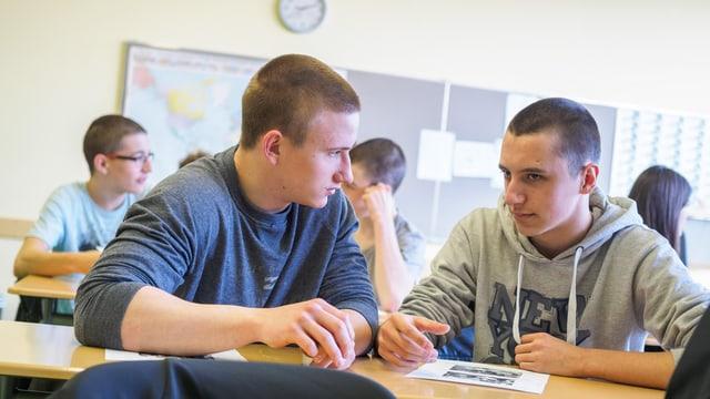Scolars en ina scola che discuteschan ensemen vid in pult
