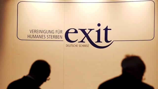 Exit-Logo an einer Wand, davor die Silhouetten von zwei Personen.