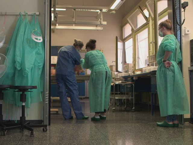 Ein paar Ärzte sind bei der Arbeit zu sehen, eine Person schaut zu.