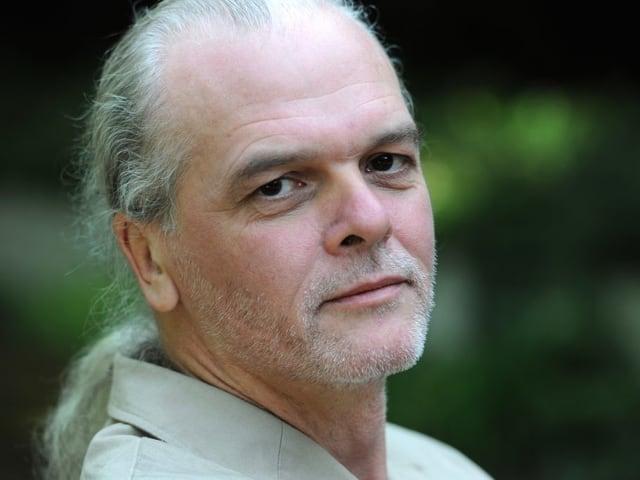 Zu sehen ein Mann mit in einen langen Zopf gebundenen, grauen Haaren und grauem Dreitagebart.