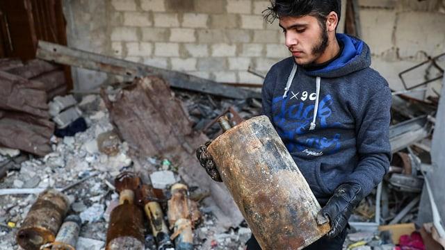 Mann der einen metallenen Zylinder in der Hand hält.