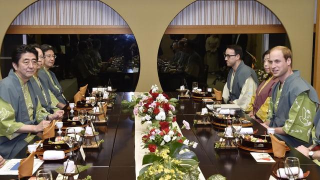 Prinz William kniet mit anderen Personen an einem feierlich gedeckten Tisch im japanischen Stil.