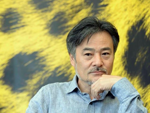 Kiyoshi Kurosawa in einem Gespräch. Im Hintergrund sieht man das gelb-schwarze Leoparden-Fell, das Markenzeichen des Filmfestival Locarno.