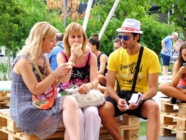 Zwei Frauen und ein Mann verpflegen sich mit Sandwiches.
