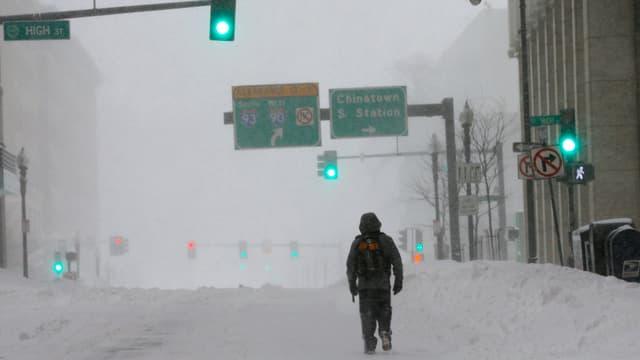 Ein Mann läuft auf schneebedeckter Strasse durch Boston.