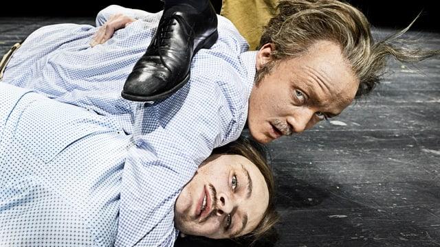 Zwei Männer im Hemd ringen am Boden miteinander.