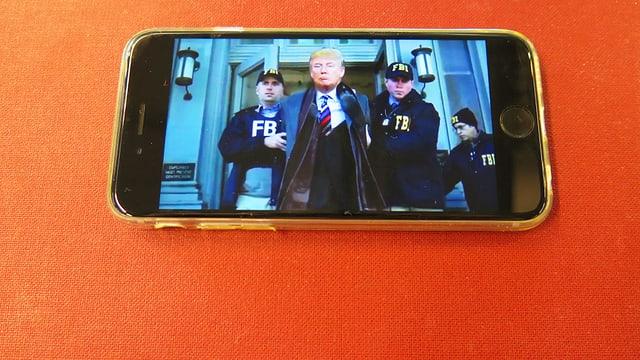 Smartphone, auf dessen Bildschirm Donald Trump zu sehen ist, der von der FBI festgenommen wird.