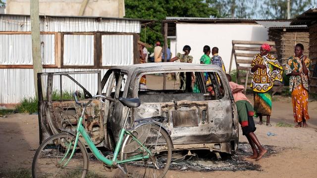 Ausgebranntes Auto auf einem afrikanischen Dorfplatz.